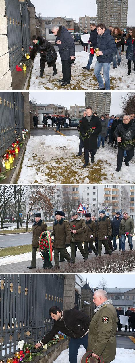 Минчане и представители общественных организаций несут цветы и лампады к посольству России в Беларуси
