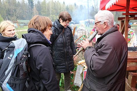 Марьян Скраблевич демонстрирует иностранным туристам белорусские музыкальные инструменты
