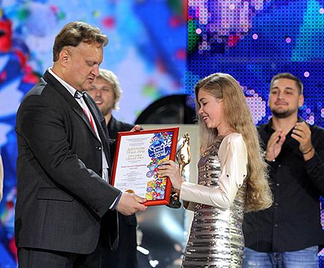 Старшыня журы конкурсу Віктар Бабарыкін уручае ўзнагароду Анастасіі Гладзілінай