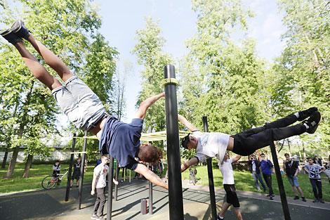 Упражнения юных атлетов на ворк-аут площадке в городском парке Вилейки